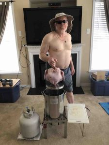 Picture of the author above deep fryer with turkey in hand in his living room (very dangerous)