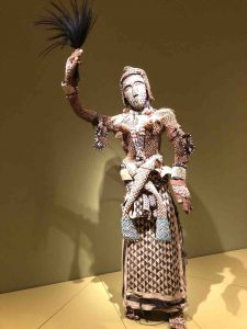 African thatched figure waving a fan